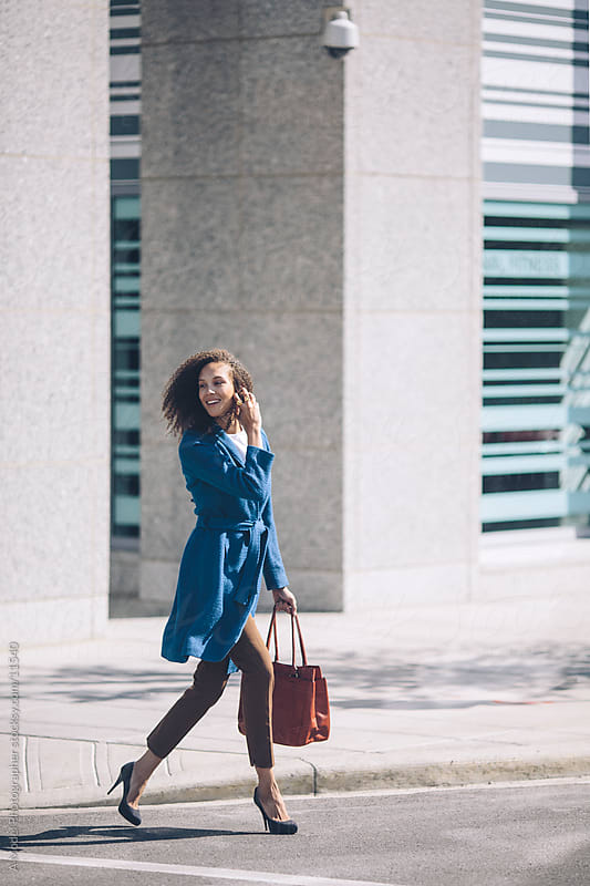 A smiling woman crossing the street by Ania Boniecka for Stocksy United