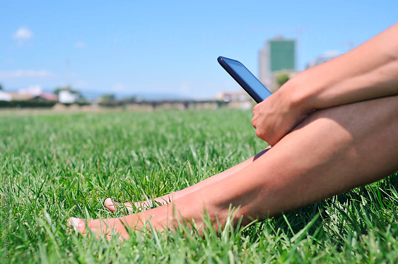 young man with a tablet on the grass by Juan Moyano for Stocksy United