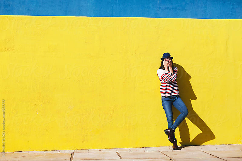 Young woman hiding her face in front of yellow background.  by BONNINSTUDIO for Stocksy United