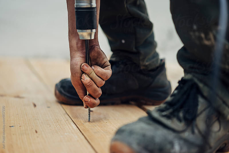 Builder using an electric screwdriver by Juri Pozzi for Stocksy United