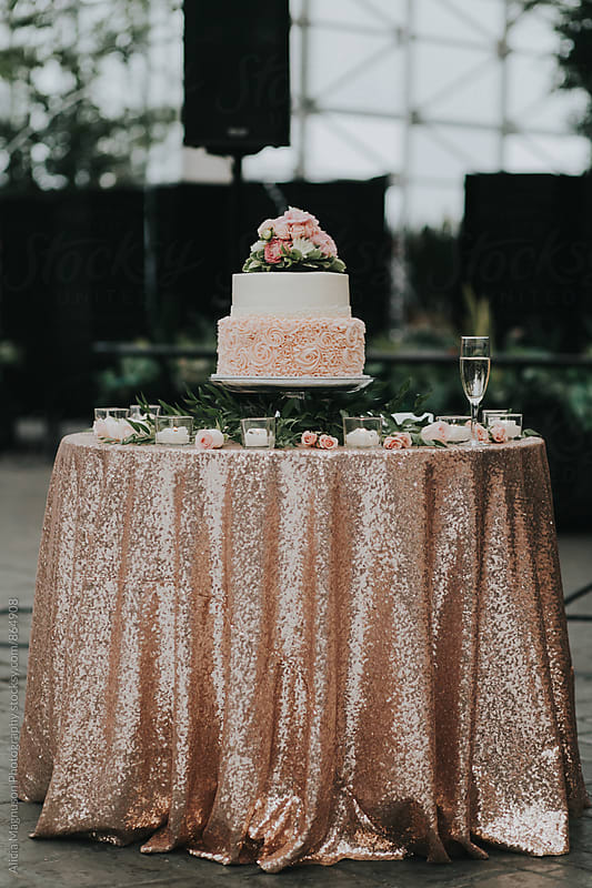 Detail of Blush Pink and White Wedding Cake on Candlelit Table with Champagne Glass by Alicia Magnuson Photography for Stocksy United