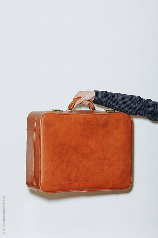 Man holding retro leather luggage / suitcase  by B & J for Stocksy United