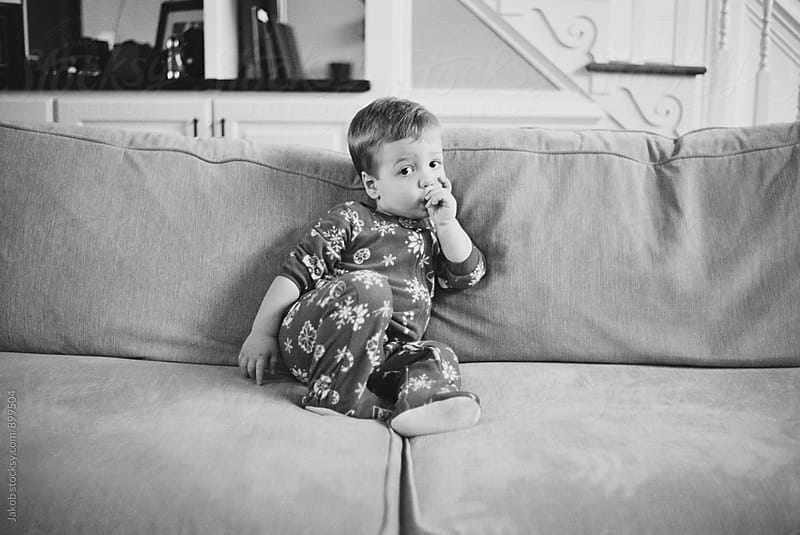 Cute young toddler in a onesie sucking his thumb while sitting on a couch by Jakob for Stocksy United