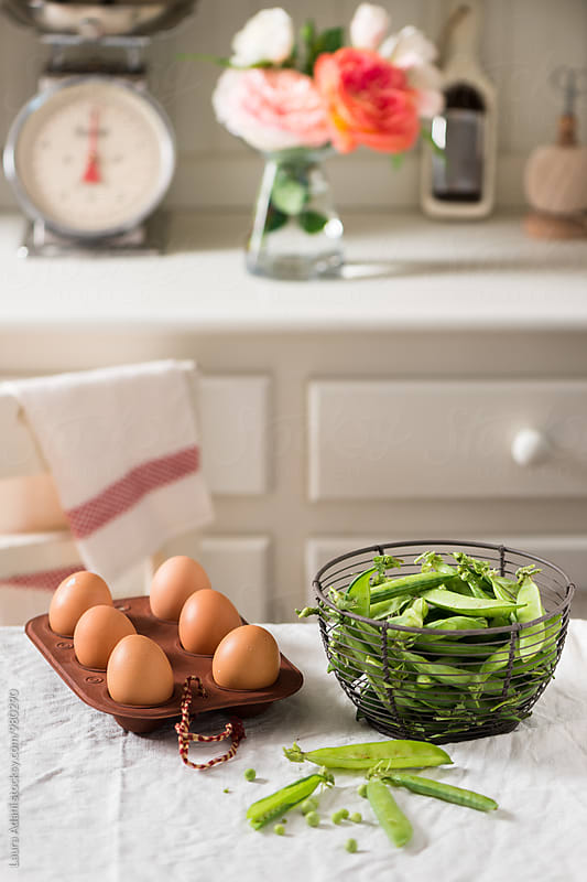 Green peas and chicken eggs in a kitchen by Laura Adani for Stocksy United