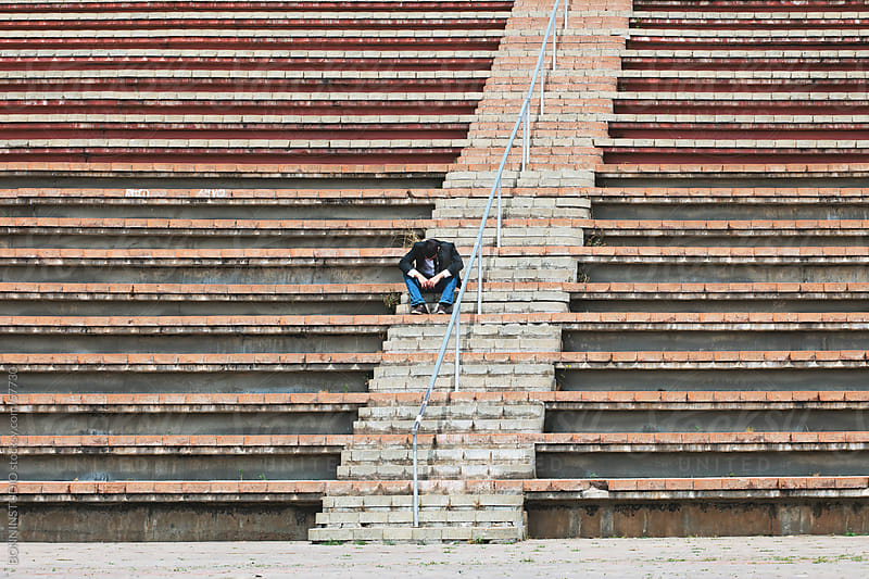 Young businesman depressed sitting on street stairs. by BONNINSTUDIO for Stocksy United