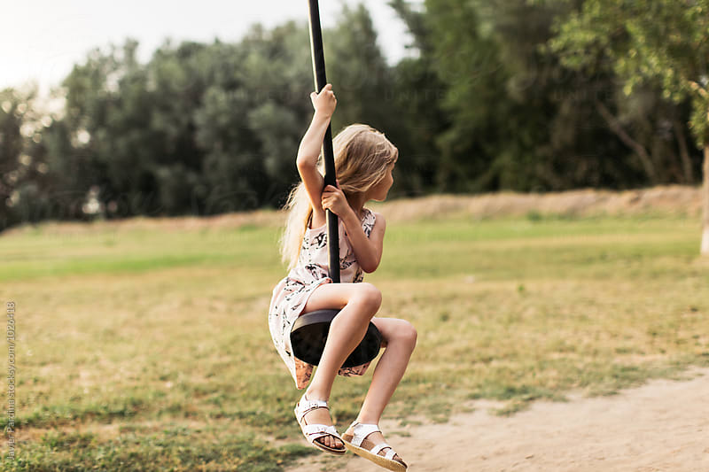 girl riding on a swing by Javier Pardina for Stocksy United