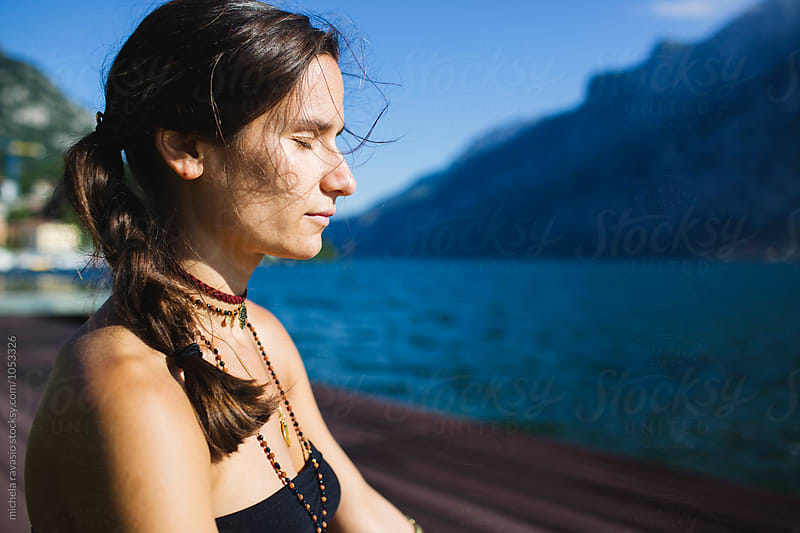 Young woman with closed eyes meditating outdoors by michela ravasio for Stocksy United