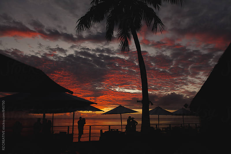Tourists enjoying a vibrant Tahitian sunset. by Robert Zaleski for Stocksy United