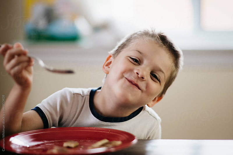 Awesome kid eating pancakes  by Cameron Whitman for Stocksy United