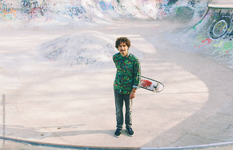 Young stylish man swinging with his skateboard in skatepark by Denni Van Huis for Stocksy United
