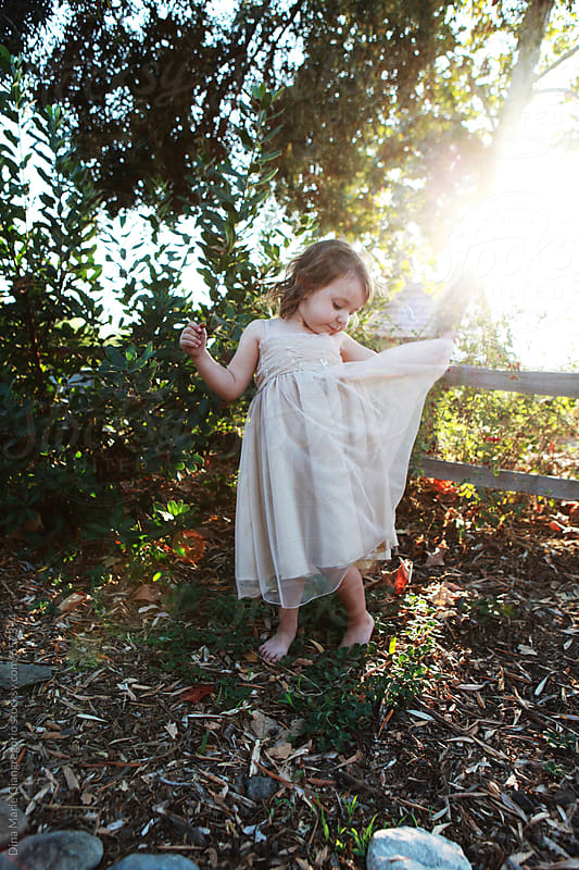 Little Girl Lifting Sweet Dress With One hand by Dina Giangregorio for Stocksy United