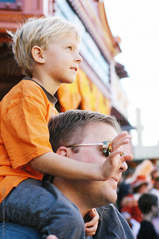 child and father watch a parade by Kelly Knox for Stocksy United