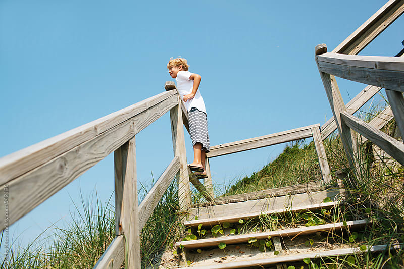 boy standing on boardwalk steps on the beach by Kelly Knox for Stocksy United