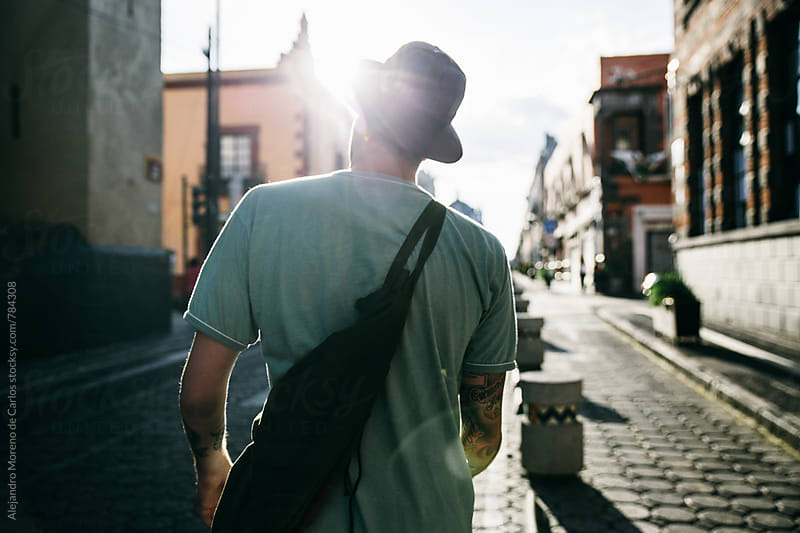 Back view of a young modern man walking on a stone street with the sun rays in front by Alejandro Moreno de Carlos for Stocksy United