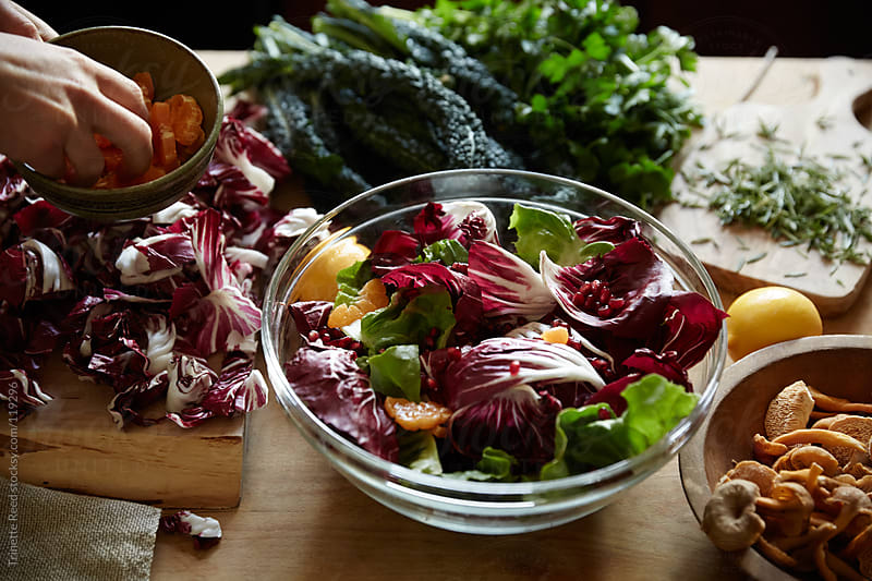 Woman making a radicchio and pomegranate, and orange salad by Trinette Reed for Stocksy United