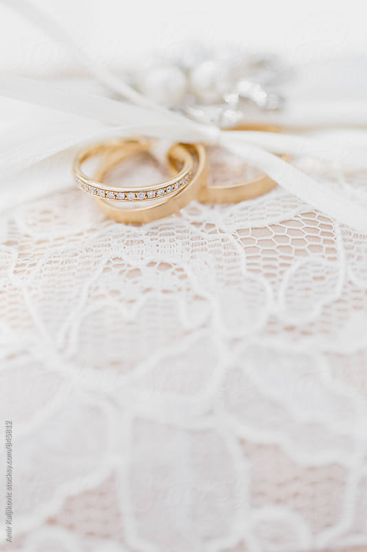 Two gold wedding bands tied with ribbon by Amir Kaljikovic for Stocksy United