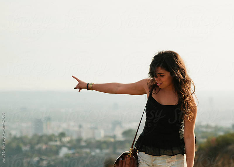 young woman points out to city skyline by Jesse Morrow for Stocksy United