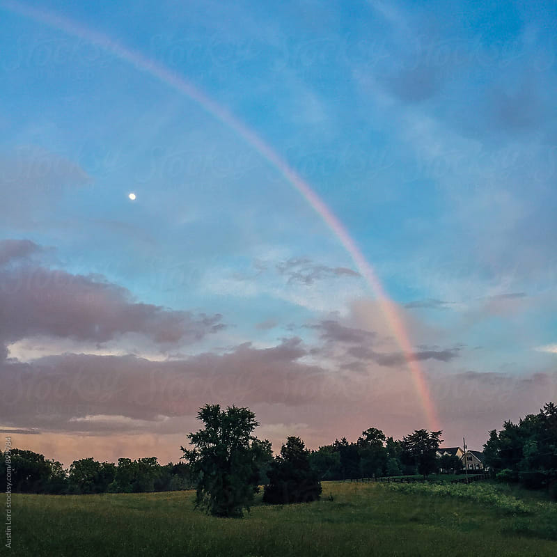 Rainbow over a house at sunset. by Austin Lord for Stocksy United