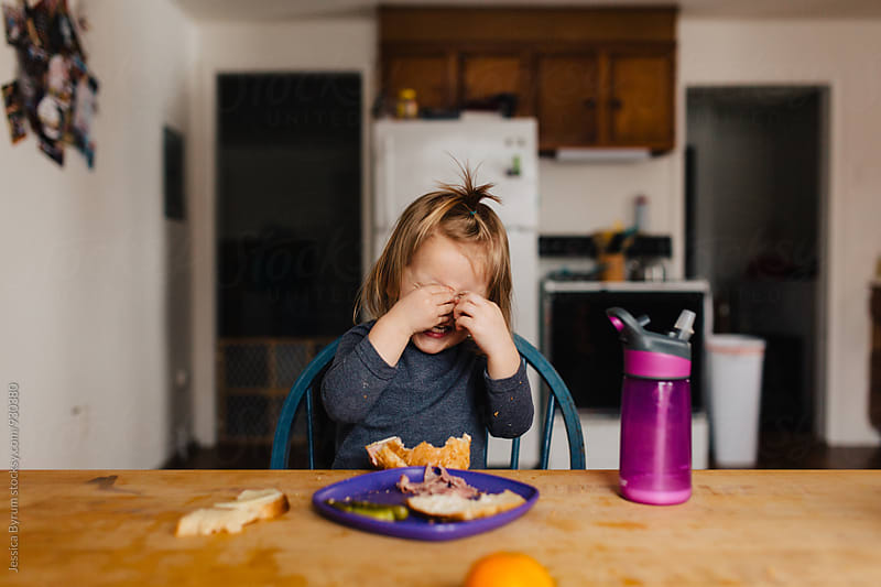 Toddler girl covering her eyes while eating lunch by Jessica Byrum for Stocksy United