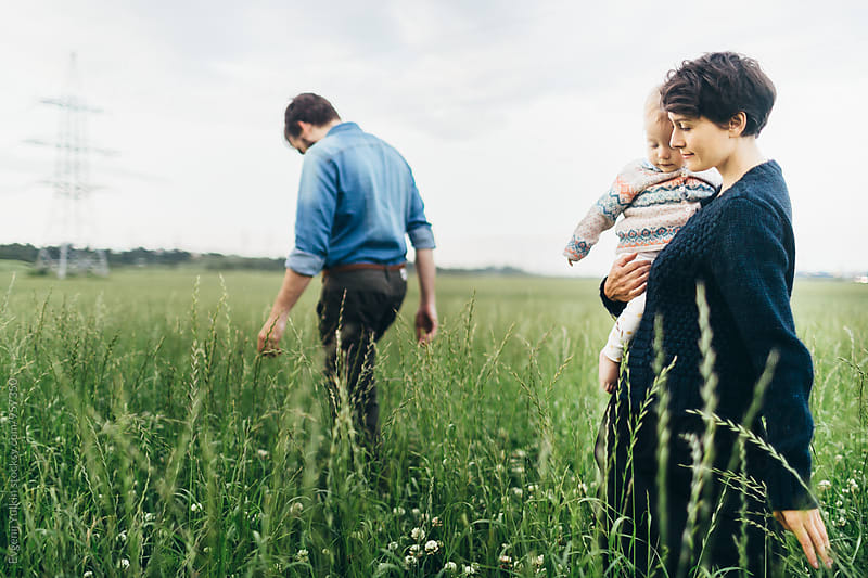 Beautiful family walking through the field by Evgenij Yulkin for Stocksy United