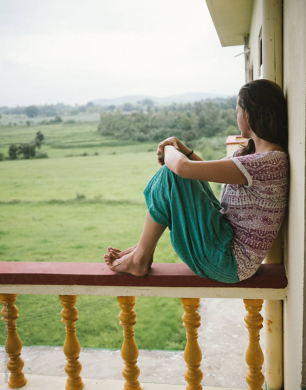 Girl Sitting on balcony railing by Martin Matej for Stocksy United