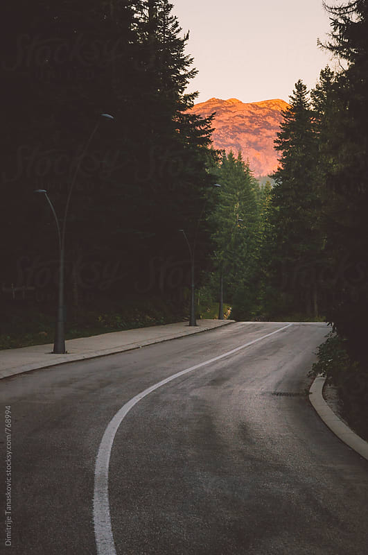 Empty road in the forest with view on the mountain peak lit by morning sun by Dimitrije Tanaskovic for Stocksy United