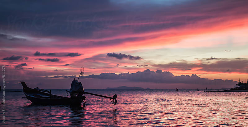 Small wooden fishing boats with beautiful sunset in background/Thailand by Marko Milanovic for Stocksy United