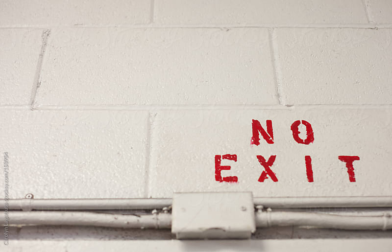 No Exit in red letters on a brick wall by Carolyn Lagattuta for Stocksy United
