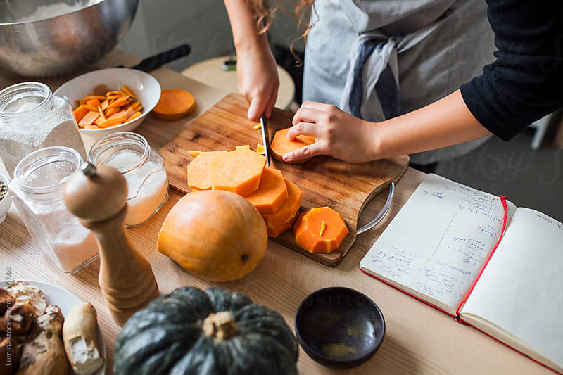 Woman Slicing a Pumpkin by Lumina for Stocksy United
