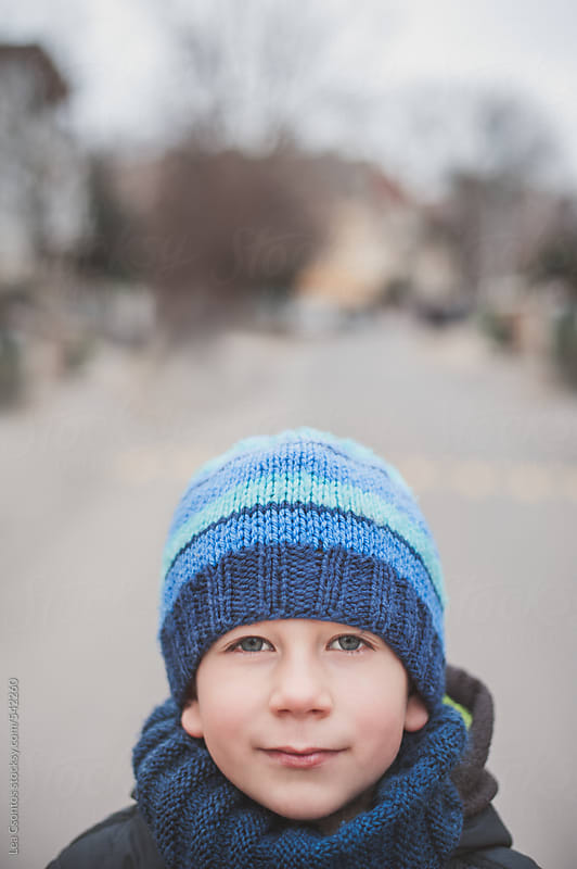 Portrait of a young boy looking at camera with a blurred street in the background by Lea Csontos for Stocksy United