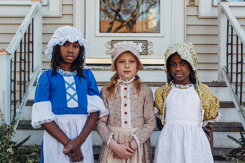 Caucasian and black girls wearing old-fashion dresses by Gabriel (Gabi) Bucataru for Stocksy United