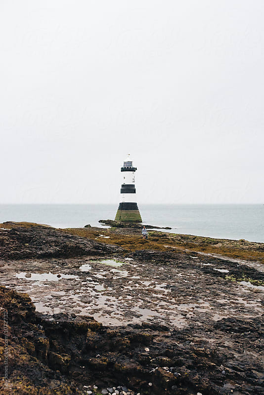 lighthouse in the evening by Léa Jones for Stocksy United