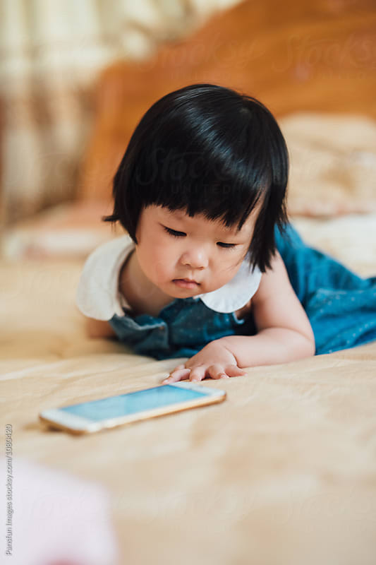 baby using cell phone by Xunbin Pan for Stocksy United