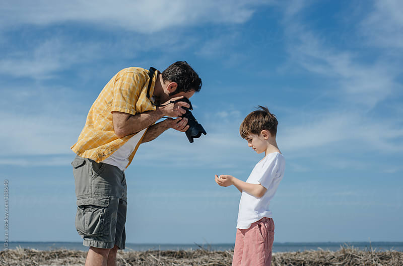 Father takes a picture of something his son has found on the beach by Cara Dolan for Stocksy United
