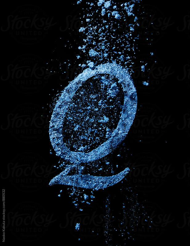 blue powder falling over letter Q by Naoko Kakuta for Stocksy United