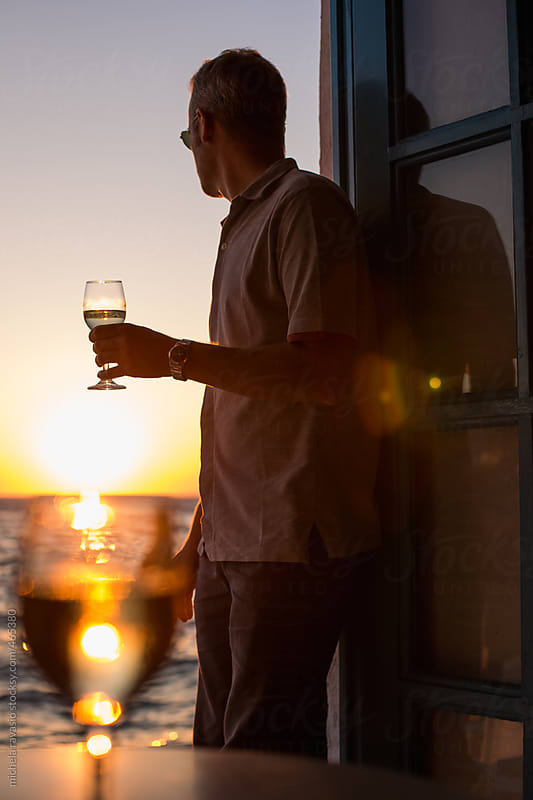 Man looking at the sunset with a glass of white wine in hand by michela ravasio for Stocksy United