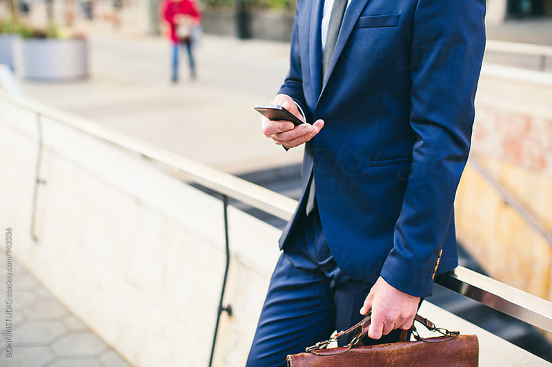 Closeup of a businessman using phone on the street. by BONNINSTUDIO for Stocksy United