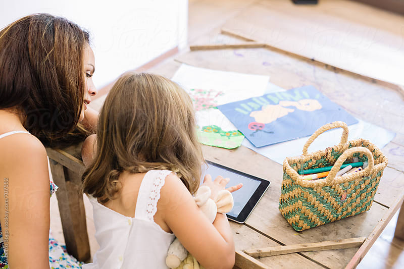 mother and daughter using a digital tablet by Alberto Bogo for Stocksy United