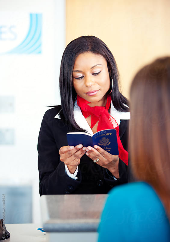 Airport: Ticket Agent Looking at Passport by Sean Locke for Stocksy United