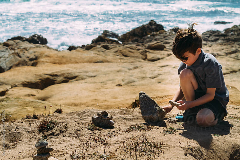 child stacking rocks near ocean by Jess Lewis for Stocksy United