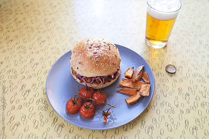 pulled / shredded pork burger on a plate with coleslaw, cherry vine tomatoes, roasted sweet potato by Natalie JEFFCOTT for Stocksy United