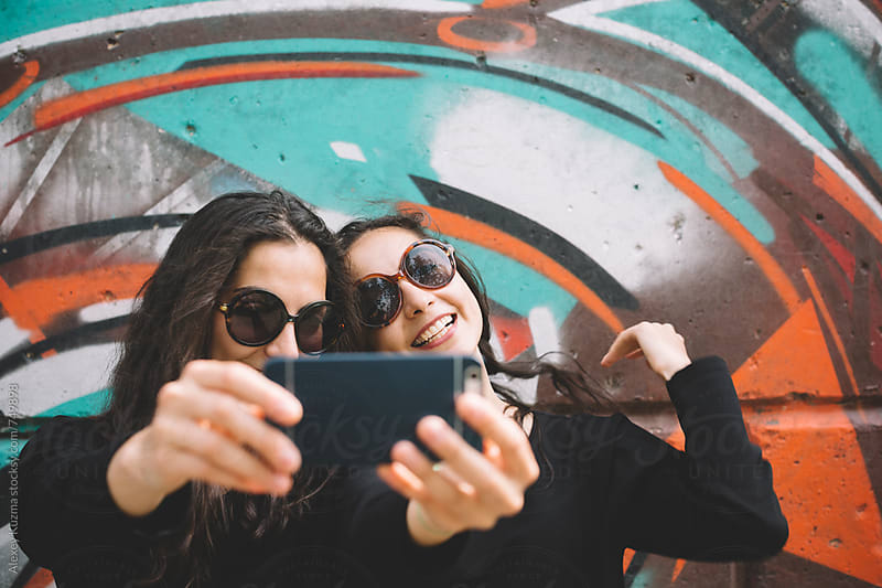 happy young women making a selfie outdoors by Alexey Kuzma for Stocksy United