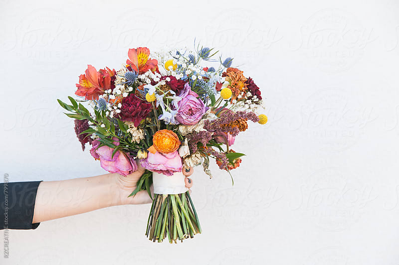 Woman's hand holding a boquet of flowers. by Robert Zaleski for Stocksy United