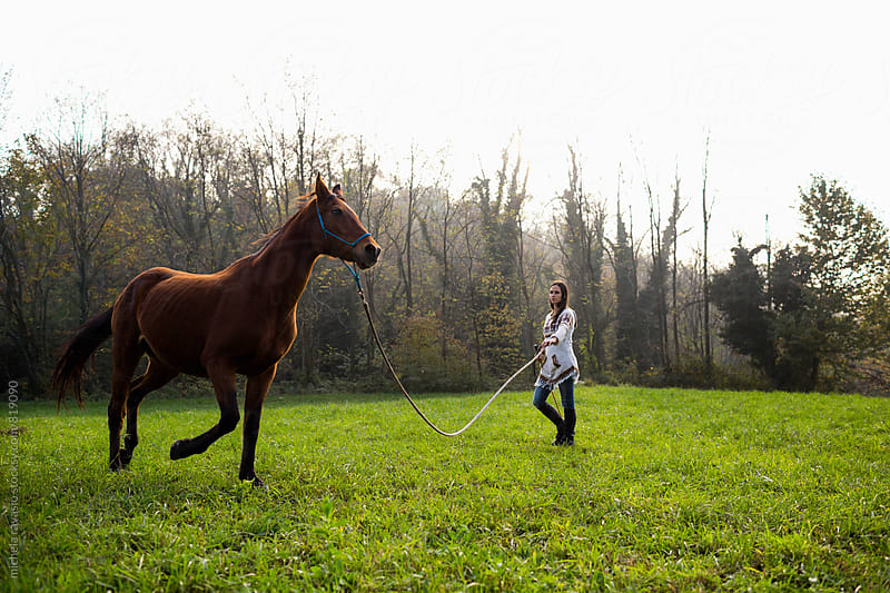 Woman practicing the exercises of Natural Horsemanship with her horse by michela ravasio for Stocksy United