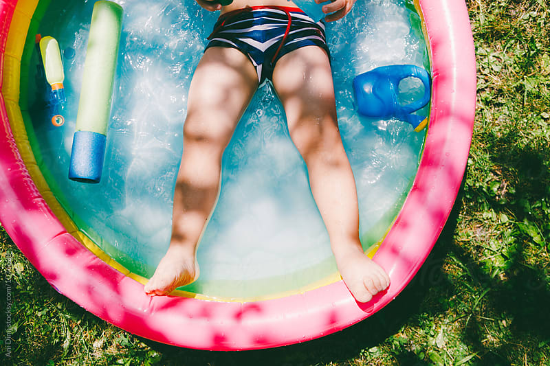 Young boy playing in kiddie pool in the backyard by Ani Dimi for Stocksy United