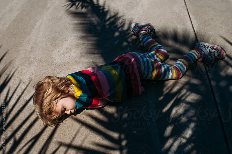 Little girl lies down on the side-walk with palm tree shadows covering her body.  by Julia Forsman for Stocksy United