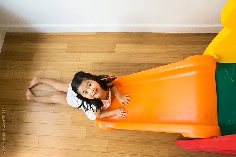 Asian girl, having fun with an indoor kid's slide by yuko hirao for Stocksy United
