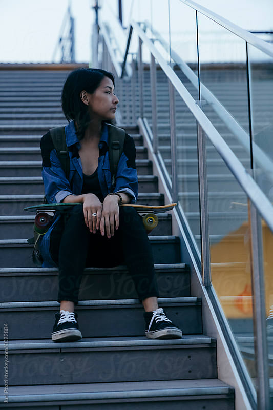 attractive young female skater relaxing on stairs by Juri Pozzi for Stocksy United