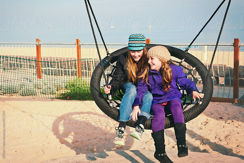 sisters on a swing by Gillian Vann for Stocksy United