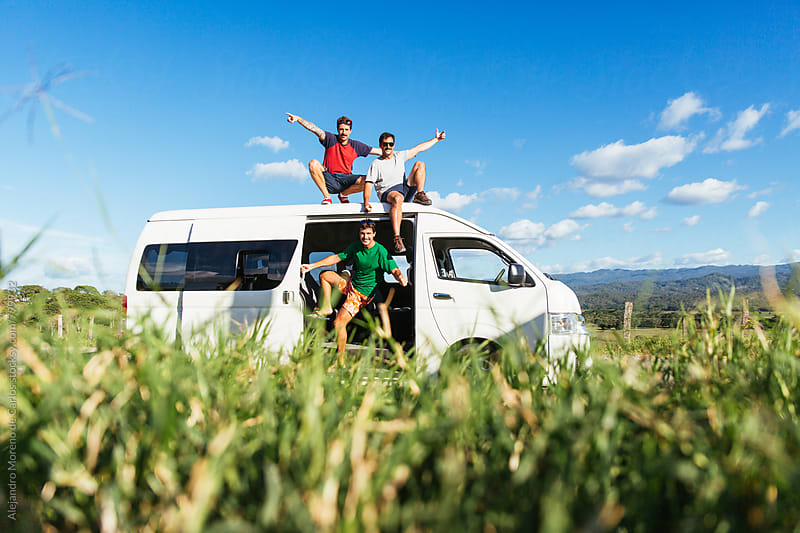 Three excited young men sitting on the roof of a white minivan during a break stopover in the middle of the road in the countryside with grass in front by Alejandro Moreno de Carlos for Stocksy United